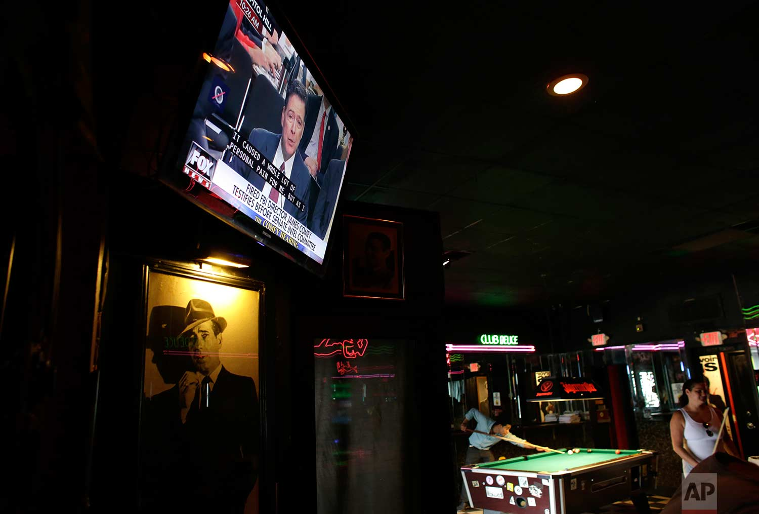 A television shows testimony by former FBI director James Comey before the Senate Intelligence Committee as patrons play pool at Mac's Club Deuce, Thursday, June 8, 2017, in Miami Beach, Fla. (AP Photo/Lynne Sladky)