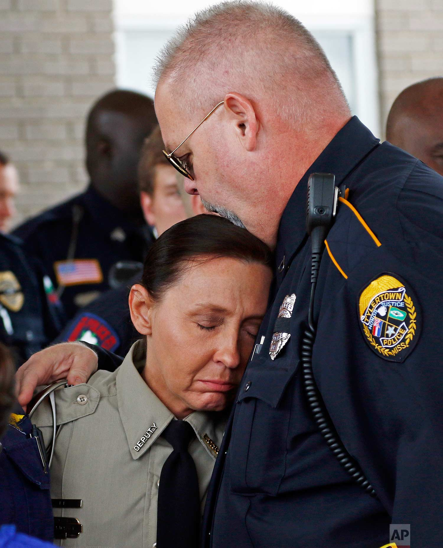 People console each other at Easthaven Baptist Church in Brookhaven, Miss., Thursday, June 1, 2017, following the funeral of Lincoln County Sheriff's Office deputy William Durr who was among eight people gunned down during a county wide killing spree that began Saturday night. (AP Photo/Rogelio V. Solis)