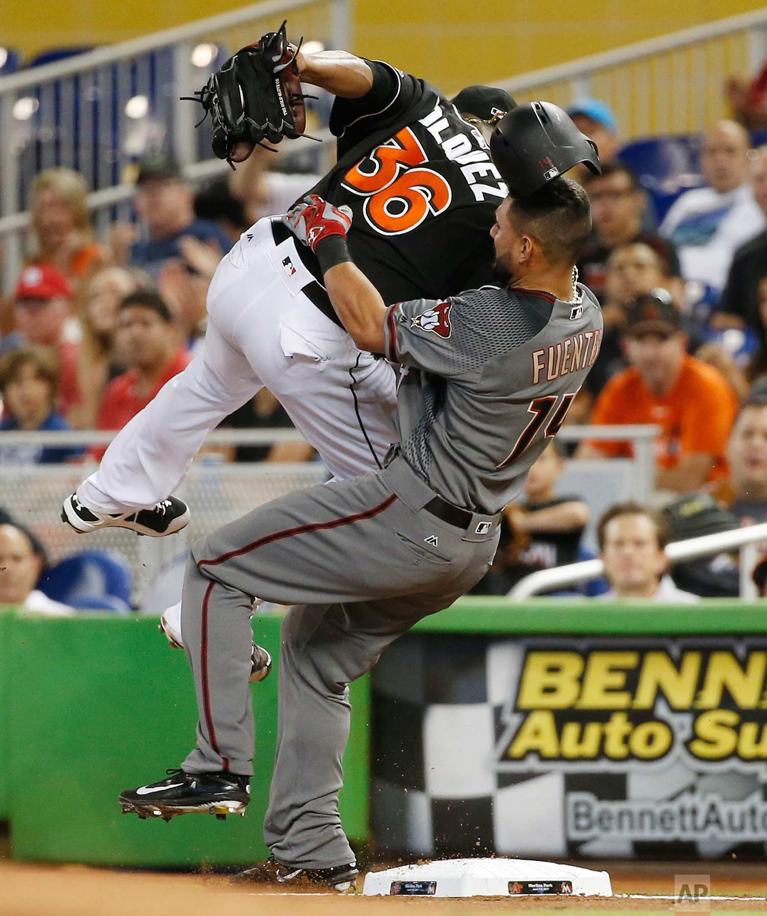 Arizona Diamondbacks' Reymond Fuentes (14) collides with Miami Marlins starting pitcher Edinson Volquez (36) after Volquez tagged first base for the out during the first inning of a baseball game, Saturday, June 3, 2017, in Miami. (AP Photo/Wilfredo Lee)