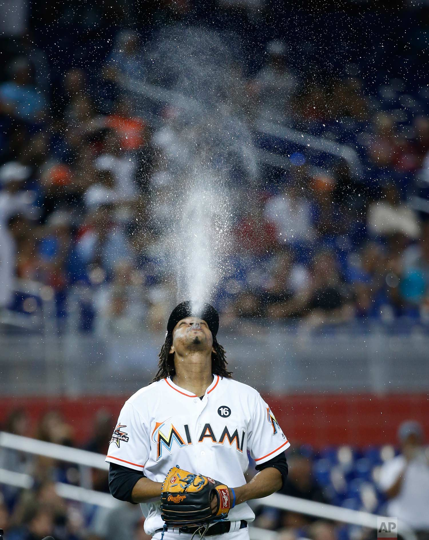 Miami Marlins starting pitcher Jose Urena spits up water as he heads to the mound during the first inning of a baseball game against the New York Mets, Thursday, June 29, 2017, in Miami. (AP Photo/Wilfredo Lee)
