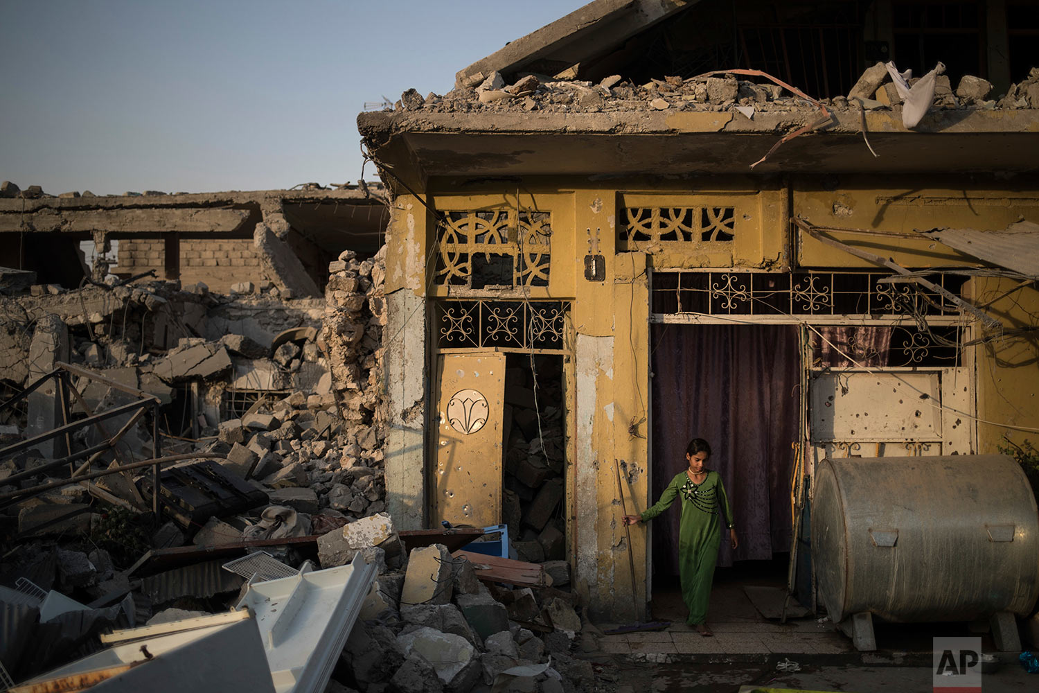 In this July 13, 2017 photo, Samaher Saddam cleans the entrance of her damaged house in the west side of Mosul, Iraq. (AP Photo/Felipe Dana)