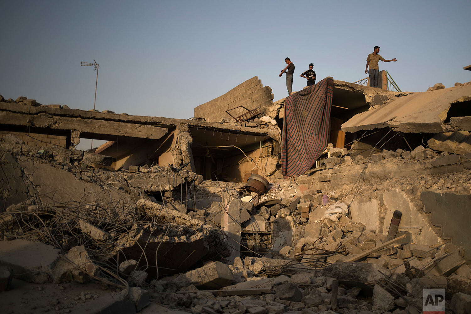 In this July 13, 2017 photo, members of the Salih Ahmed family stand on the roof of their partially damaged house in the west side of Mosul, Iraq. (AP Photo/Felipe Dana)