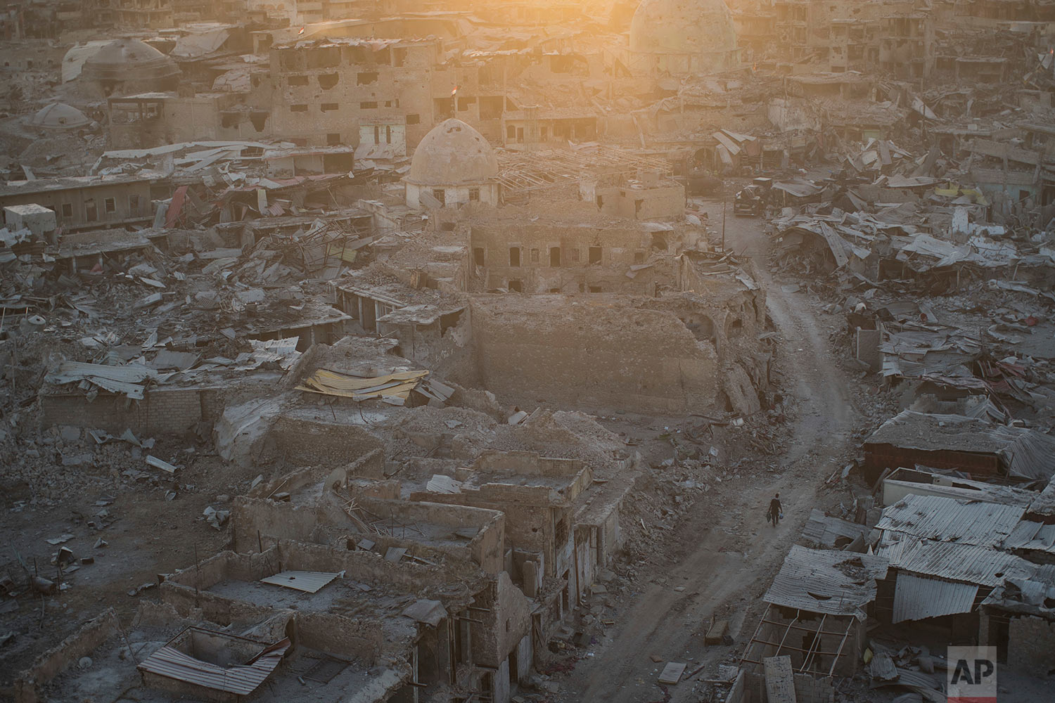 In this July 11, 2017 photo, a soldier carries supplies through a damaged neighborhood as the sun sets in the west side of Mosul, Iraq. (AP Photo/Felipe Dana)