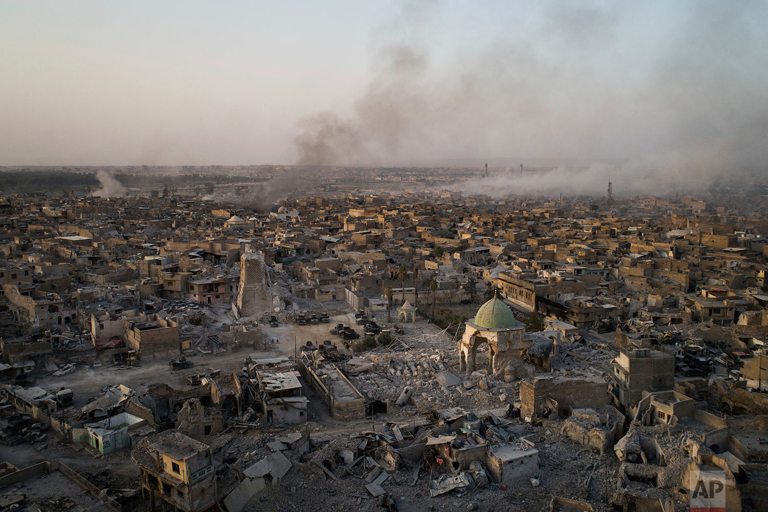 In this July 4, 2017 photo, the heavily damaged al-Nuri mosque sits as smoke from explosions billow from the Old City of Mosul, Iraq. (AP Photo/Felipe Dana)
