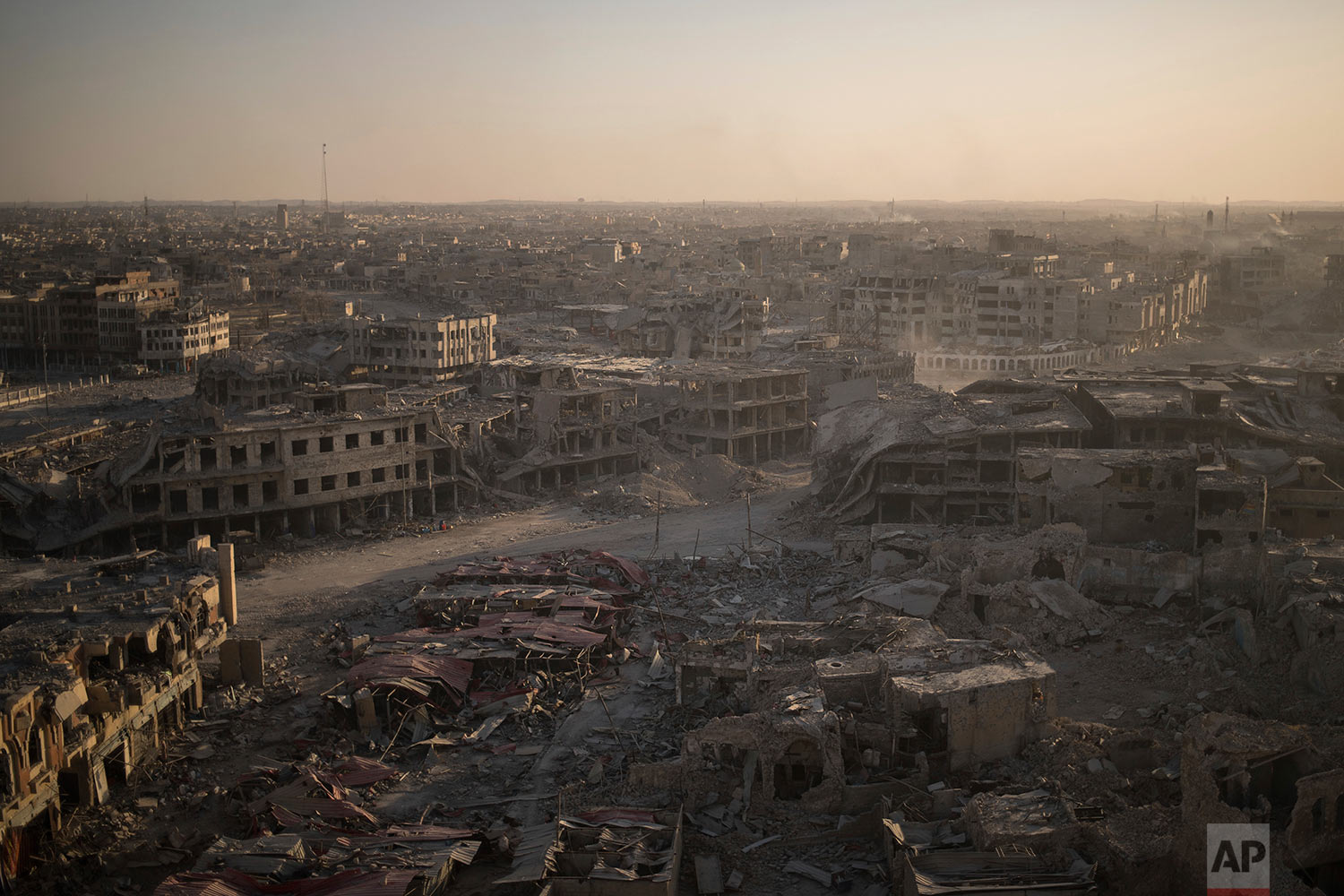 In this July 11, 2017 photo, damaged buildings are lit by the setting sun in the west side of Mosul, Iraq. (AP Photo/Felipe Dana)