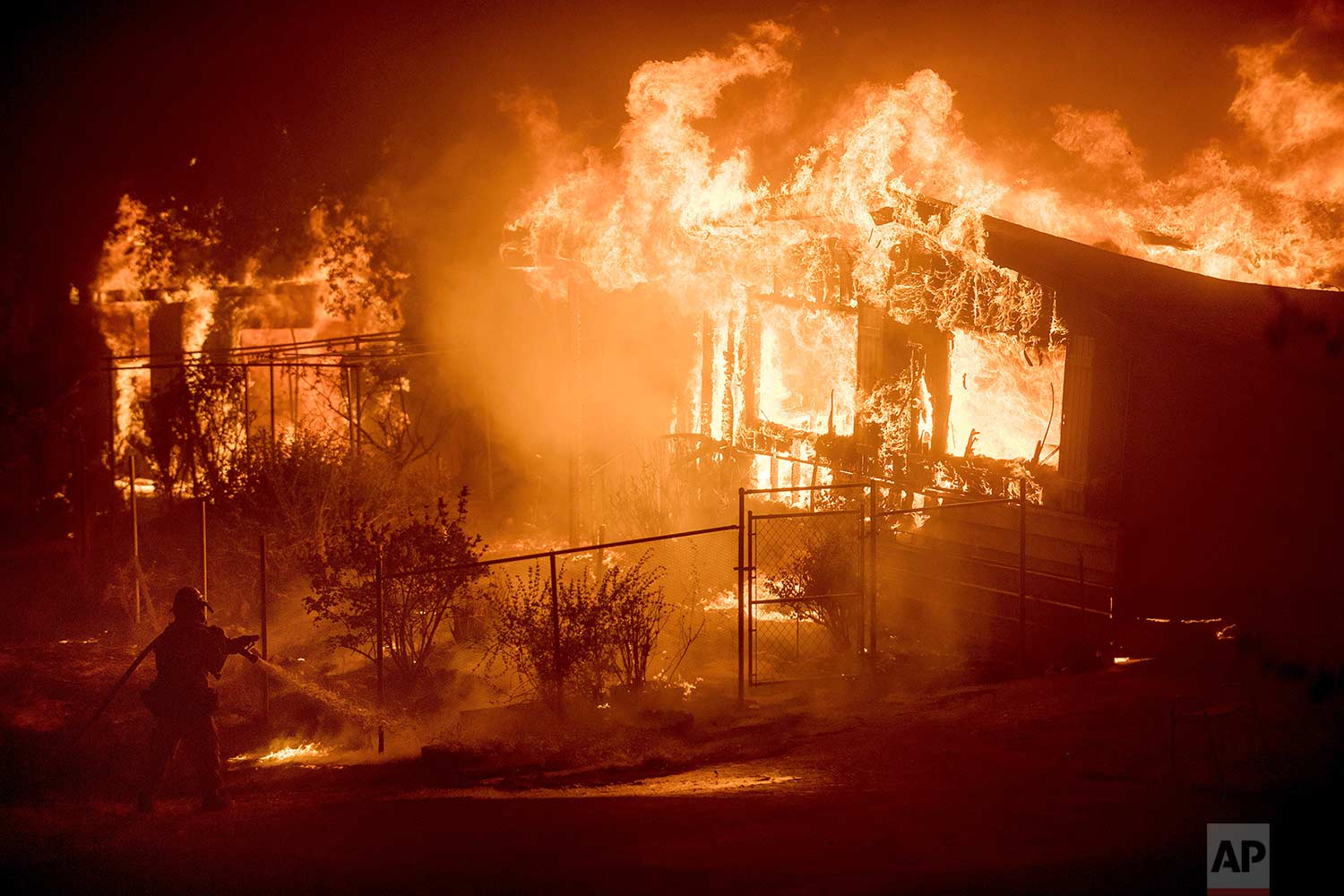 A firefighter sprays water as flames from a wildfire engulf a residence near Oroville, Calif., on Sunday, July 9, 2017. (AP Photo/Noah Berger)