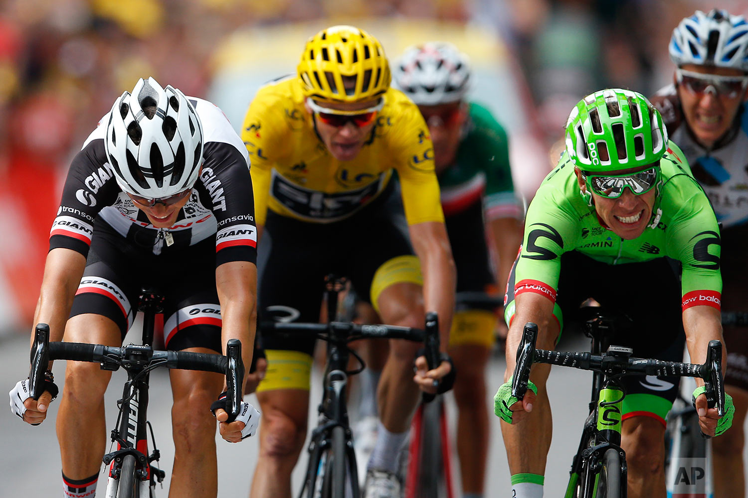 Colombia's Rigoberto Uran, right, crosses the finish line ahead of ahead of France's Warren Barguil, left, Britain's Chris Froome, wearing the overall leader's yellow jersey, Italy's Fabio Aru, third from left, and France's Romain Bardet, far right, to win the ninth stage of the Tour de France cycling race over 181.5 kilometers (112.8 miles) with start in Nantua and finish in Chambery, France, Sunday, July 9, 2017. (AP Photo/Peter Dejong)