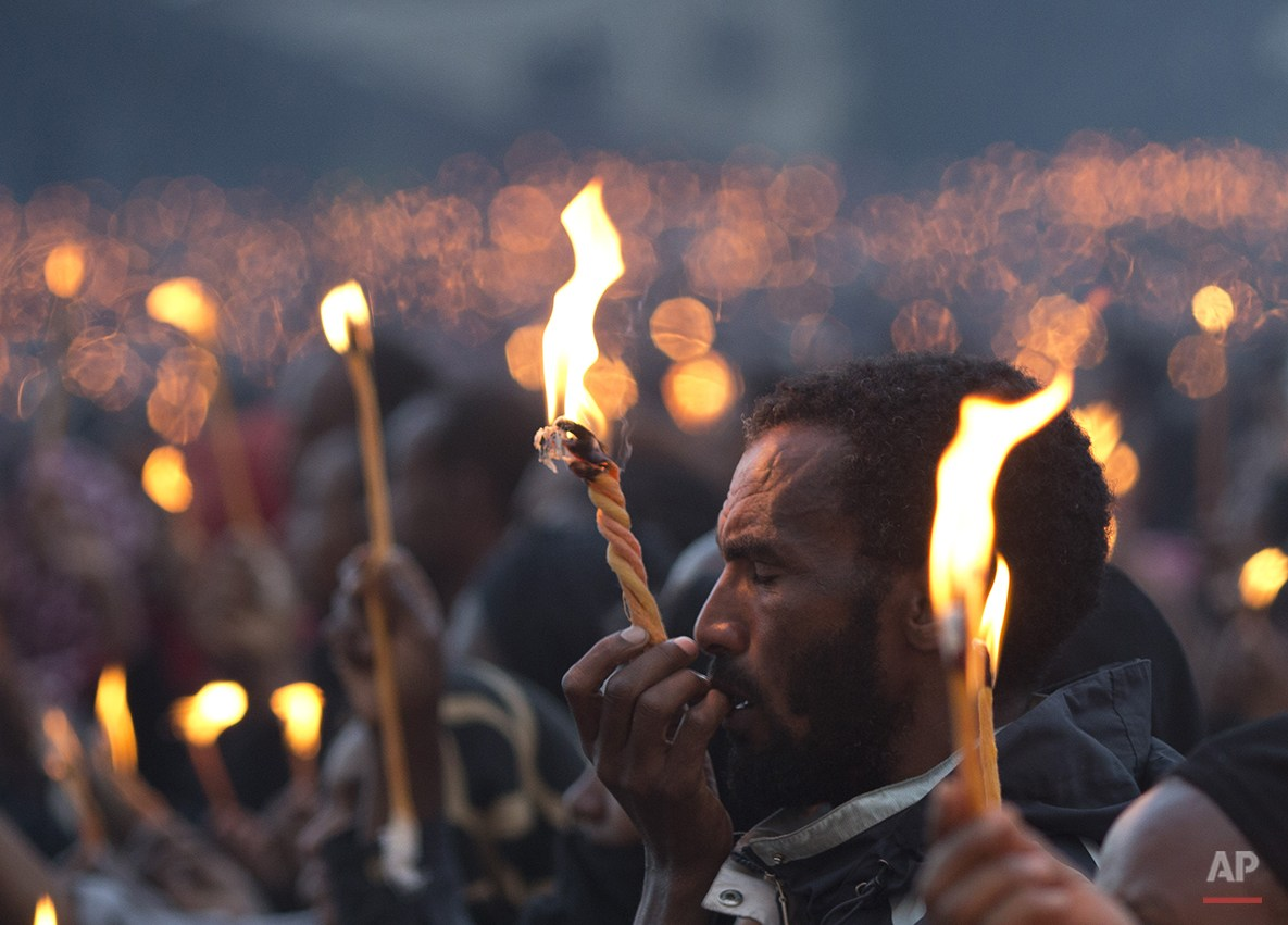 A man closes his eyes as he holds up his candle during a public candlelight memorial for late Prime Minister Meles Zenawi, at Meskel Square in Addis Ababa, Ethiopia Thursday, Aug. 30, 2012. Thousands turned out for the first of three days of planned commemorative ceremonies. Zenawi will be buried on Sunday, Sept. 2.(AP Photo/Rebecca Blackwell)