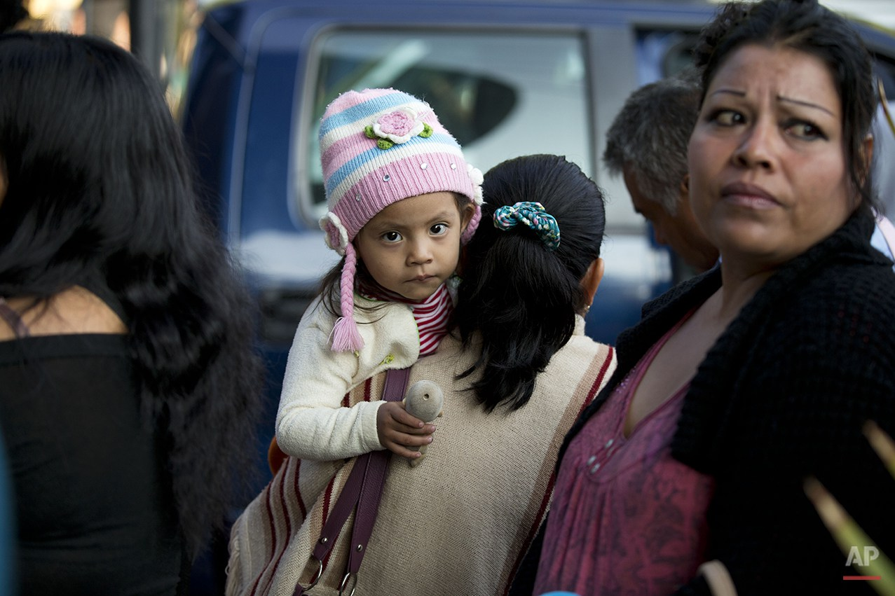 Relatives wait to be reunited with children and adults living at The Great Family group home, which police cordoned off in Zamora, Michoacan State, Mexico, Thursday, July 17, 2014. The relatives of youths rescued by police from a refuse-strewn group home where employees allegedly beat and raped residents are telling how they tried to remove their loved ones, only to be met with demands for thousands of dollars for their release. (AP Photo/Rebecca Blackwell)