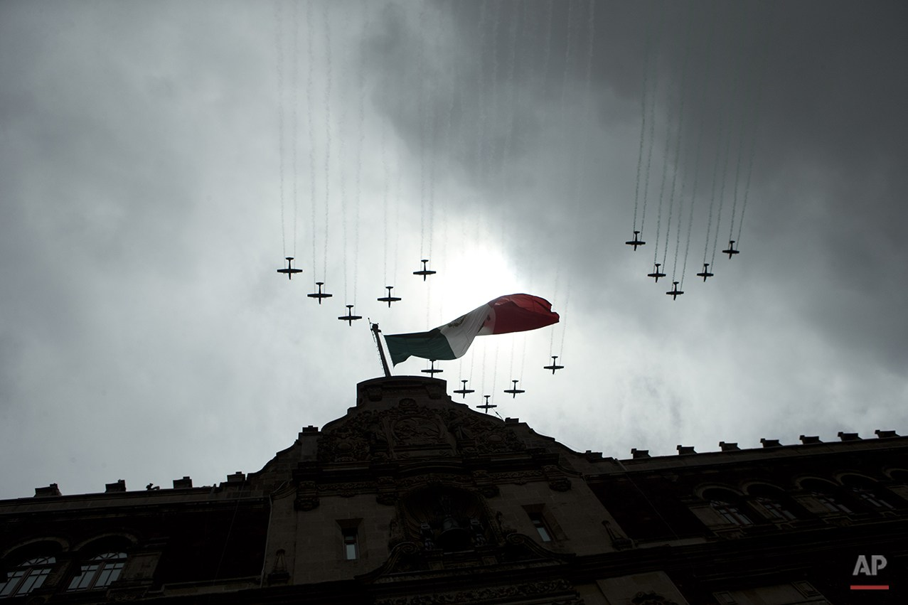 Mexican airforce aircraft, trailing the colors of the national flag fly over the National Palace during the finale of an annual Independence Day parade by Mexico's Armed Forces, in the Zocalo in central Mexico City,Tuesday, Sept. 16, 2014. Mexico is marking the 204th anniversary of its independence from Spain. (AP Photo/Rebecca Blackwell)
