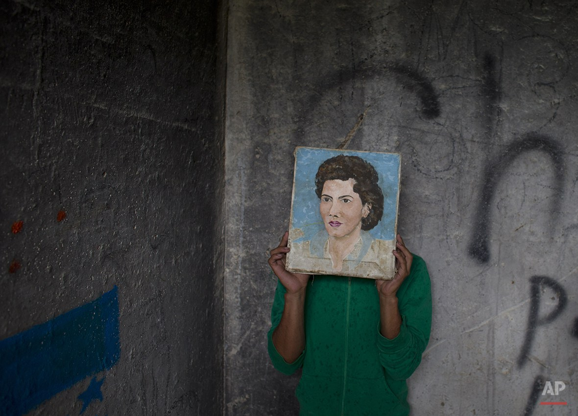 In this Wednesday, July 30, 2014 photo, a young Honduran migrant who didn't want his face to appear in photos hides behind a painting he found in a guard shack, while waiting with a group of migrants for a northbound train, in Huehuetoca, outside Mexico City. The migrant was one of three young Honduran brothers traveling north together in hopes of finding work in the U.S. Days earlier, they said, they had been robbed along with two dozen other passengers while riding a train. (AP Photo/Rebecca Blackwell)