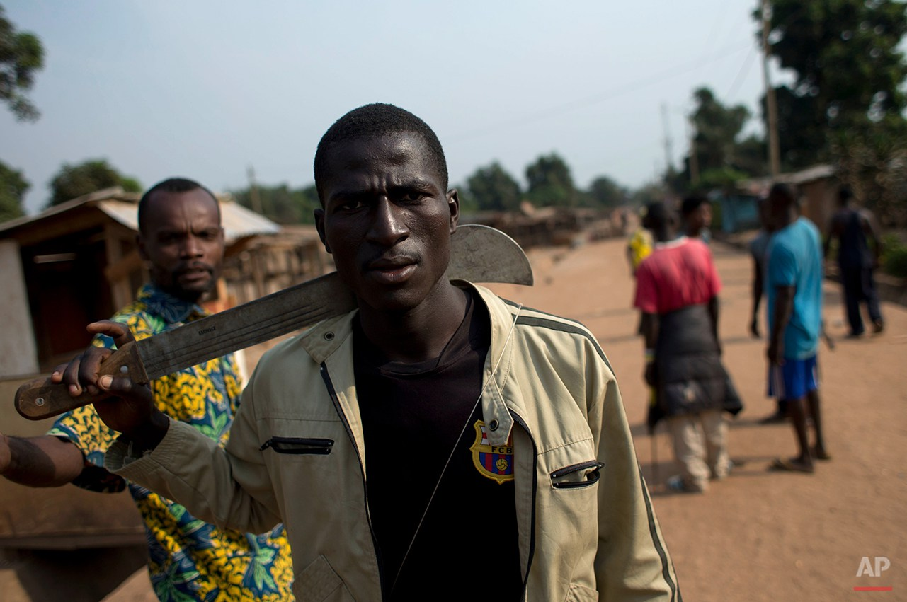 A member of an armed neighborhood defense squad, which residents say is not anti-balaka, but local Christian residents protecting themselves, carries a machete as he walks near a roadblock in Bangui, Central African Republic, Tuesday, Dec. 31, 2013. (AP Photo/Rebecca Blackwell)
