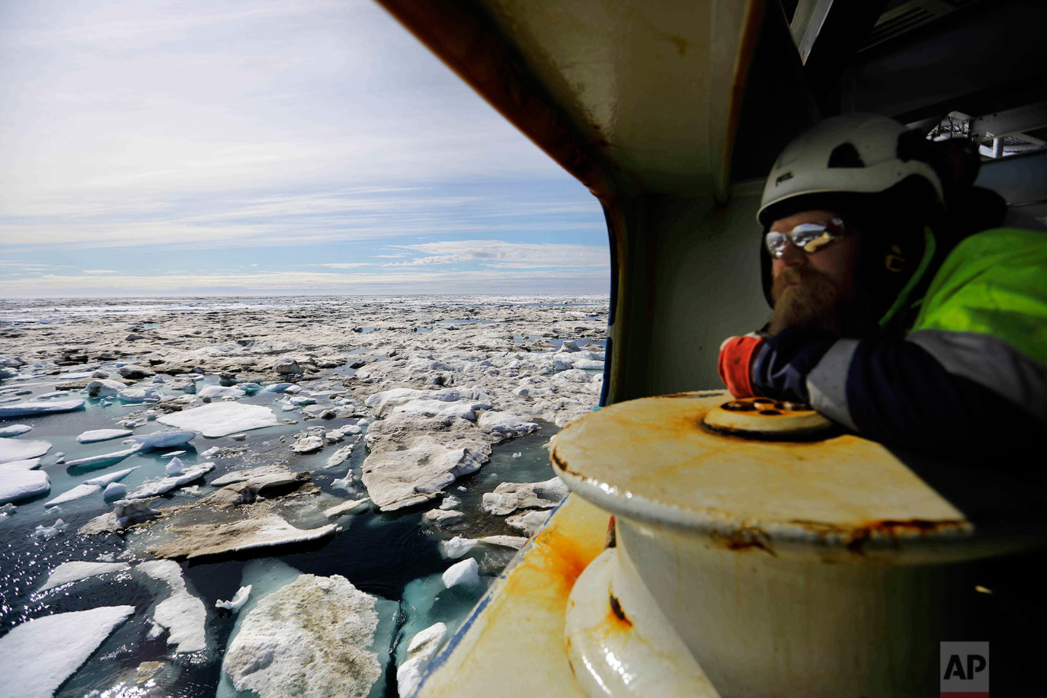 Trainee Jussi Mikkotervo looks out from the bow of the Finnish icebreaker MSV Nordica as it sails through ice floating on the Beaufort Sea off the coast of Alaska while traversing the Arctic's Northwest Passage, Sunday, July 16, 2017. Although the passage presents an attractive shortcut for maritime traffic between the Pacific and Atlantic oceans, only a dozen or two vessels attempt to navigate the poorly charted Canadian Arctic Archipelago during the brief summer window each year. (AP Photo/David Goldman)