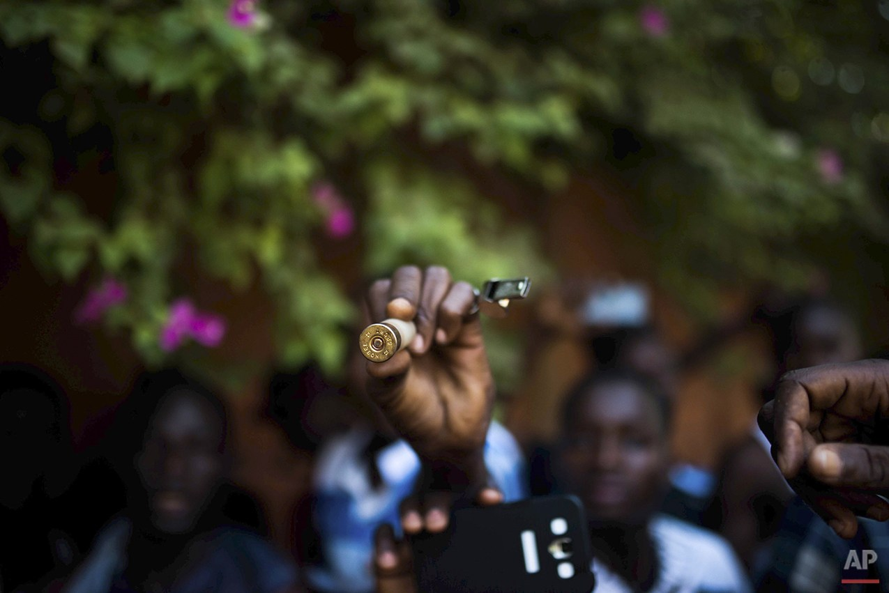 In this photo taken Thursday, Oct. 30, 2014, a protester hold up a bullet as they go on a rampage near the parliament building in Burkina Faso as people protest against their longtime President Blaise Compaore who seeks another term, in Ouagadougou, Burkina Faso. Protesters stormed the parliament Thursday, dragging furniture and computers onto the street and setting the main chamber ablaze, in the most significant challenge to the president's rule during his 27 years in power. (AP Photo/Theo Renaut)
