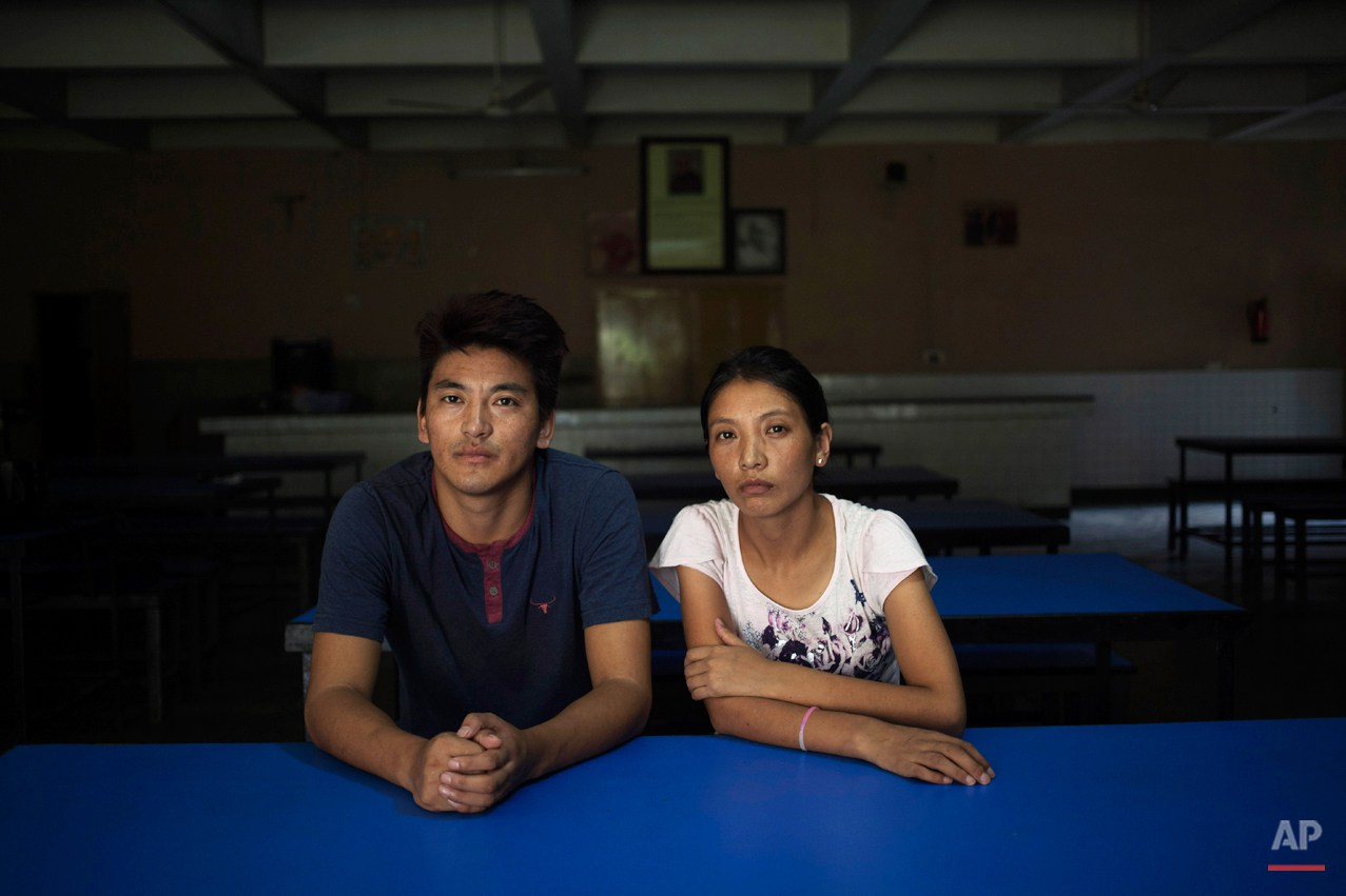In this Monday, Aug. 18, 2014 photo, Gyalsten, 26, and his sister Kyipa pose in the dining hall of the Tibetan Youth Hostel in New Delhi, India. The duo escaped into India in 2006. Gyaltsen was given the responsibility of taking care of his younger sister. This, he says, has made him a better person. They are afraid that they may never see their parents again. (AP Photo/Tsering Topgyal)