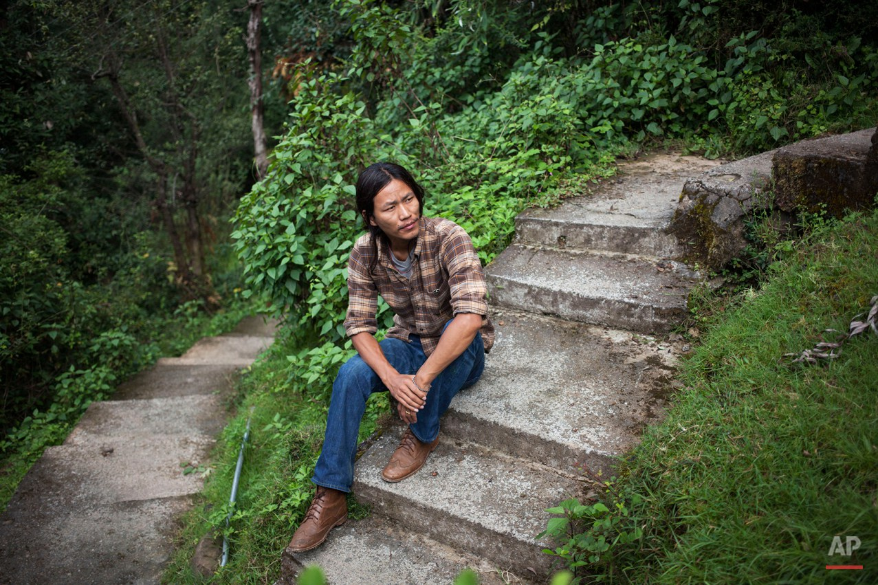 In this Thursday, Sept. 25, 2014 photo, exile Tibetan Tsering Choephel, 26, rests on concrete stairs in Dharmsala, India. Choephel left his home in Tibet 23 years ago. Sometimes, he dreams of seeing his family again. Often, he mourns the fact that he barely misses them. (AP Photo/Tsering Topgyal)
