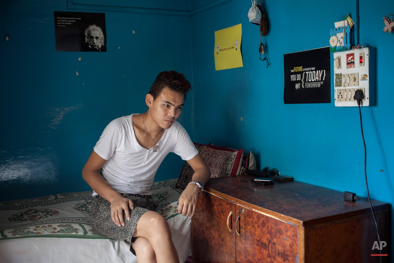 In this Wednesday, July 30, 2014 photo, Tibetan exile Kalsang Tsering, 20, sits in his room in New Delhi, India. Tsering said he missed his family when he was ill and in hospital with nobody to care for him. He now rents a room from a woman who treats him like a son and says the feeling of being cared for is wonderful. (AP Photo/Tsering Topgyal)