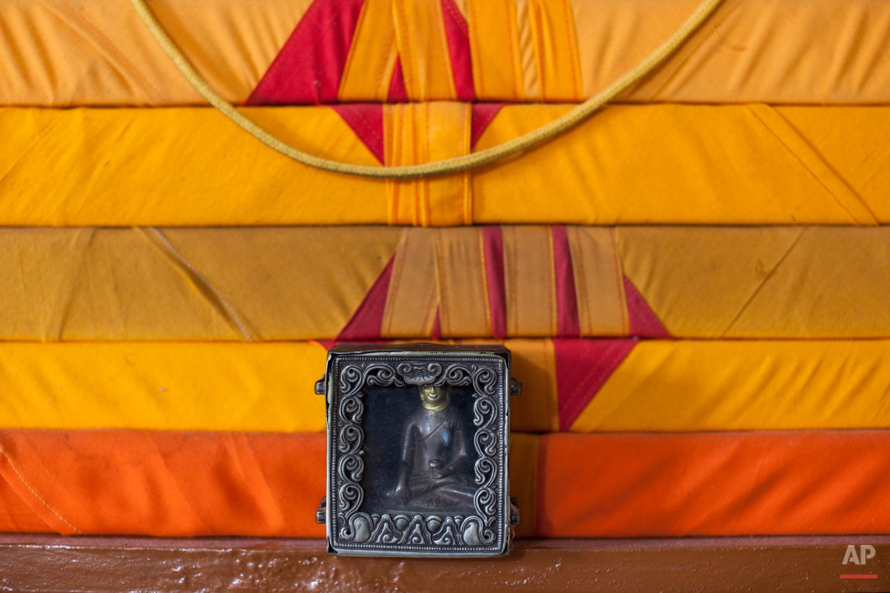 "In this Tuesday, Sept. 30, 2014 photo, an amulet containing a Buddha statue stands near scriptures in the home of Tibetan exile Sonam Gyaltsen, 44, near Dharamsala, India. Gyaltsen, who is now a member of the Tibetan parliament-in-exile, carried the amulet with him as a family keepsake when he escaped into India in 1993. ""There is technology that connects me to my family back home in Tibet now but I worry about their health,î he said. (AP Photo/Tsering Topgyal)"