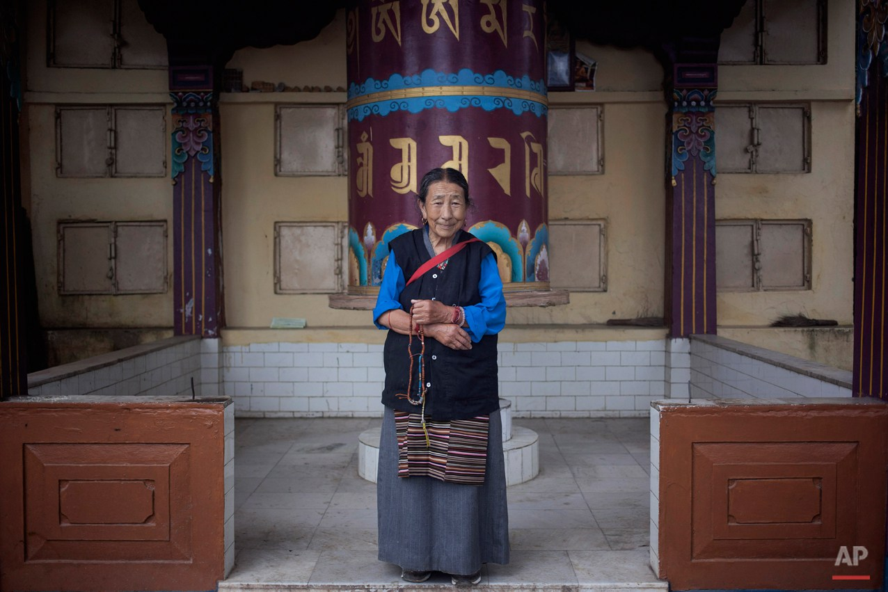 In this Thursday, Sept. 25, 2014 photo, Sonam Dolma, 75, poses for a photo near a prayer wheel in Dharamsala, India. Dolma escaped from Tibet in 1959 and made Dharmsala her home. She says she wishes to visit Tibet someday. (AP Photo/Tsering Topgyal)