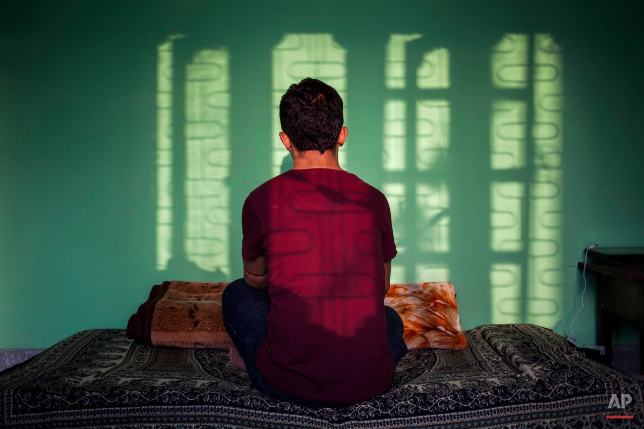 In this Sunday, Sept. 14, 2014 photo, a 27-year-old Tibetan boy, who did not want to disclose his identity, sits in his room in New Delhi, India. He escaped into India in 1992 and says the 22 years away from his family has made him strong and emotionless. His mother has grown old and conveys her yearning to meet him but he doubts whether he will get a visa. The Tibetan says he misses his parents when he watches family based dramas and movies. (AP Photo/Tsering Topgyal)