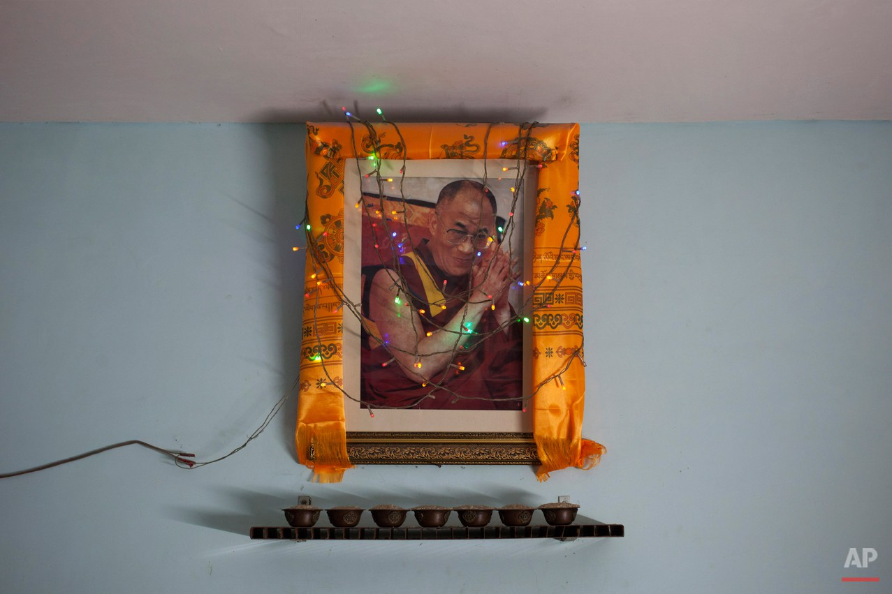 In this Tuesday, Oct. 28, 2014 photo, a portrait of Tibetan spiritual leader the Dalai Lama hangs on a wall in a restaurant in New Delhi, India. Since the Dalai Lama fled a failed 1959 uprising against Chinese rule, tens and thousands of Tibetans have taken refuge in India, taking a weekslong walk to cross over the Himalayas from Tibet to India. (AP Photo/Tsering Topgyal)