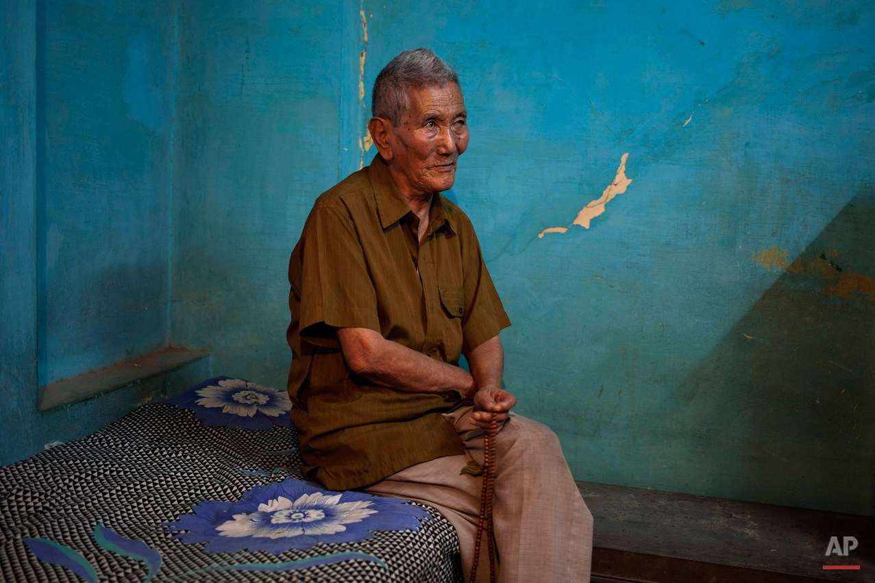 In this Wednesday, Oct. 15, 2014 photo, Kalsang Wangdue, 85, sits on a bed in his room in New Delhi, India. Wangdue says his father was a tax collector back in Tibet and he lived a good life. He escaped into India in 1959 leaving behind his wife and son. He revisited Tibet in 1993 where his wife and son pleaded he stay back but he returned to India. He says he feels lonely especially when he falls ill and sometimes wishes he remarried.  (AP Photo/Tsering Topgyal)
