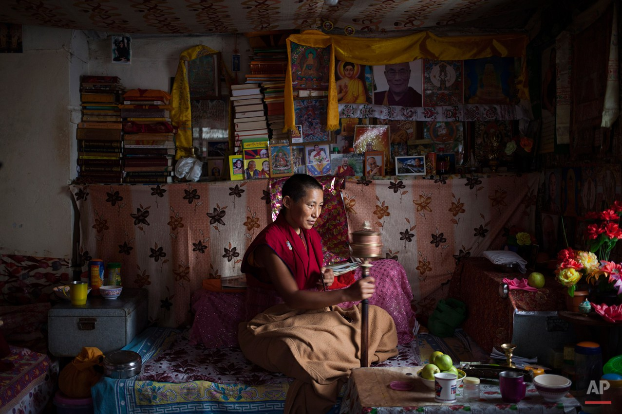 In this Saturday, Sept. 27, 2014 photo, an Exile Tibetan nun Namdak Choeying, 44, prays in her room that she shares with two other nuns in Dharmsala, India. Back home in Tibet she aspired to be a fully ordained nun and escaped to India in 2006. Her five siblings and aged parents live in Tibet and she dreams about being reunited with them. Choeying said she immerses herself in prayers to keep her mind occupied. (AP Photo/Tsering Topgyal)