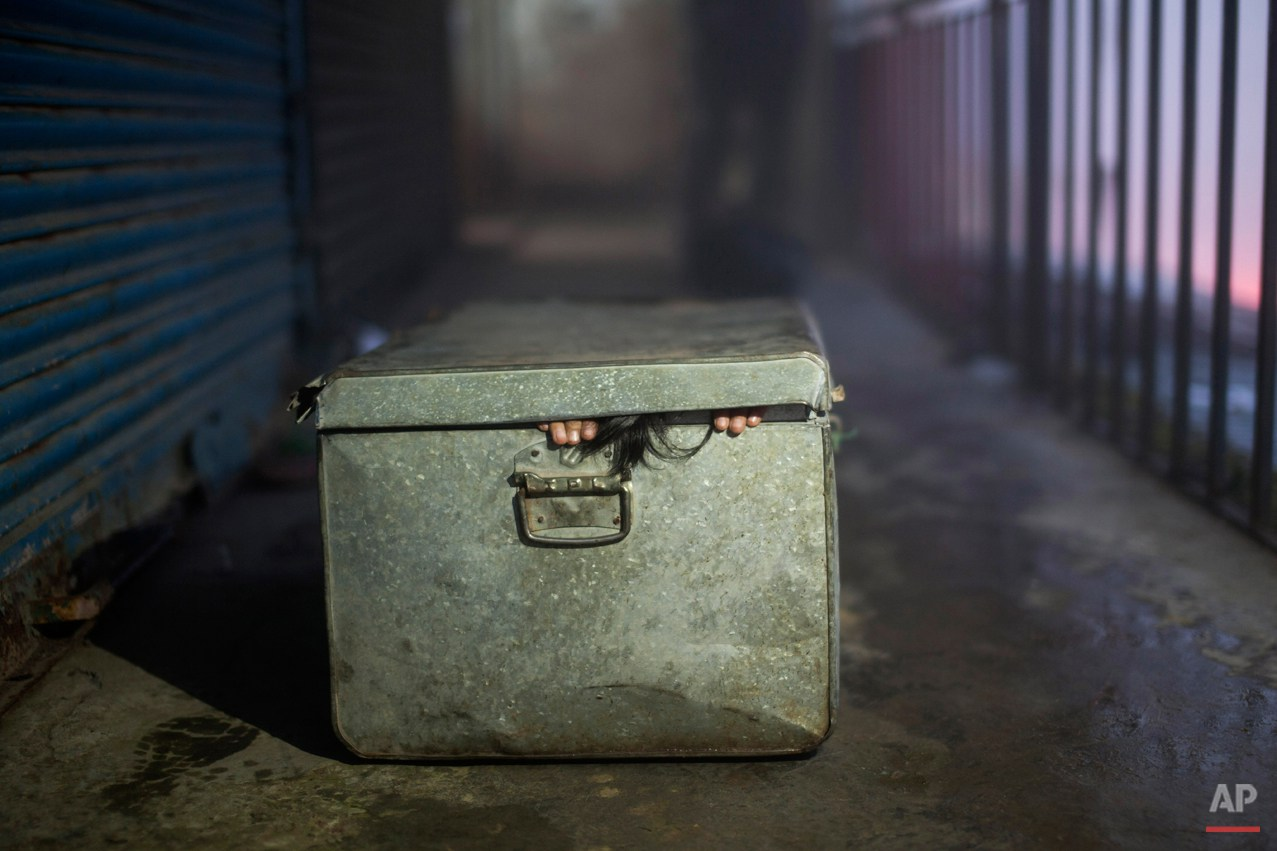 In this Sunday, Sept. 28, 2014 photo, a young Tibetan exile Pema Lhamo, 8, fits herself into a box to enact her escape scene, in Dharmsala, India. Lhamo fled to India when she was 3 years old in a box and now lives with her grandmother. She is presently studying in a Tibetan Children's Village School. (AP Photo/Tsering Topgyal)