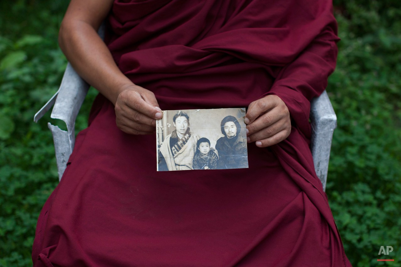 In this Saturday, Sept. 27, 2014 photo, Tibetan monk Dorjee, 38, displays a photograph of his father, left, and himself, center, taken in Tibet, in Dharamsala, India. Dorjee said he held back his tears when he spoke with his parents on the phone after a separation period of 27 years. He exchanged a few words with his father but said his mother fainted on hearing his voice. (AP Photo/Tsering Topgyal)