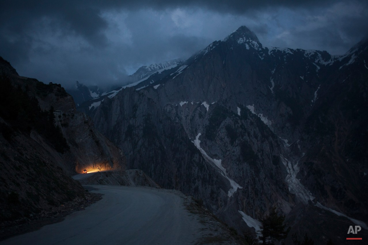 In this Monday, June 30, 2014 photo, a car moves on a serpentine road past snow-capped peaks near Zoji La in Indian-Kashmir, India. Many Tibetans say that being in the mountains make them miss their homeland. (AP Photo/Tsering Topgyal)