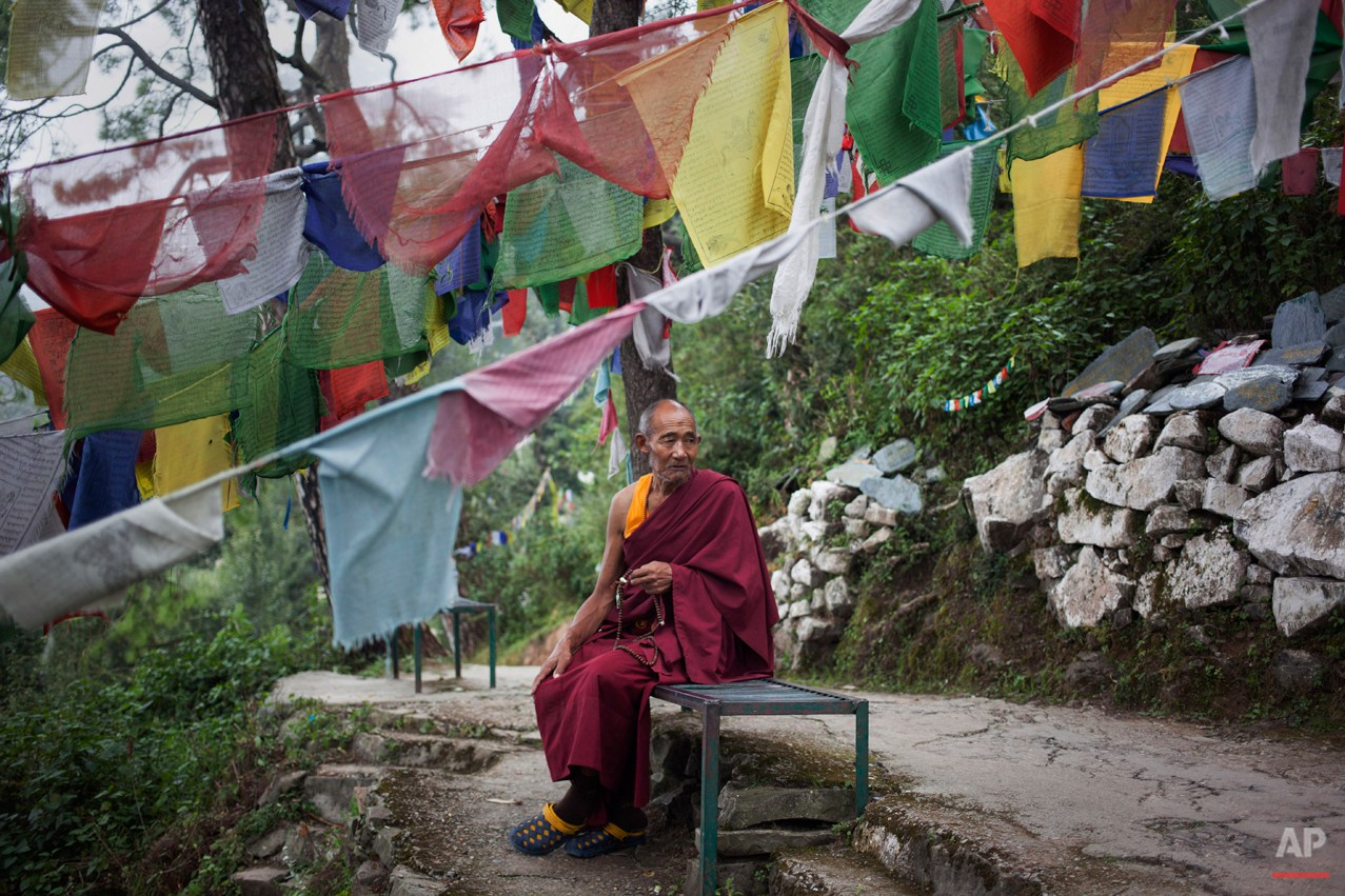 In this Thursday, Sept. 25, 2014 photo, Tibetan exile monk Lobsang Tenzin, 76, sits near prayer flags in Dharmsala, India. Tenzin lives in a home for the aged supported by the Tibetan government-in-exile. He fled Tibet in 2006 leaving his entire family behind. (AP Photo/Tsering Topgyal)