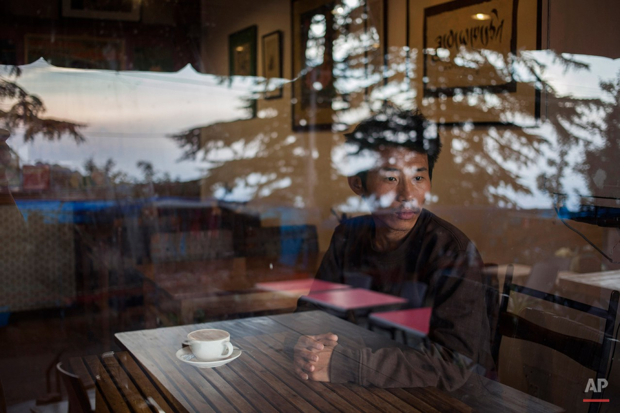 In this Tuesday, Sept. 30, 2014 photo, Tashi Dorjee  27, sits in a coffee shop in Dharmsala, India. He fled with his brother as a four-year-old in 1991. Dorjee says he missed his parents most when he was in school, especially when everyone went home for winter vacation as he had no home to go to. He says because of time and distance there is no attachment with family and parents. (AP Photo/Tsering Topgyal)