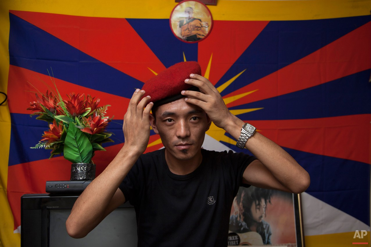 "In this Friday, June 6, 2014 photo, Exile Tibetan Dorjee Tashi adjust the beret he calls ""Che Guevera cap"" as he poses for a photograph in front of a flag of Tibet in his room in New Delhi, India. Tashi had just returned from a protest rally when he received news of his fatherís death in a voice message stored on his phone. His one wish was to meet his father again and considers this unfulfilled wish as part of his karma. (AP Photo/Tsering Topgyal)"