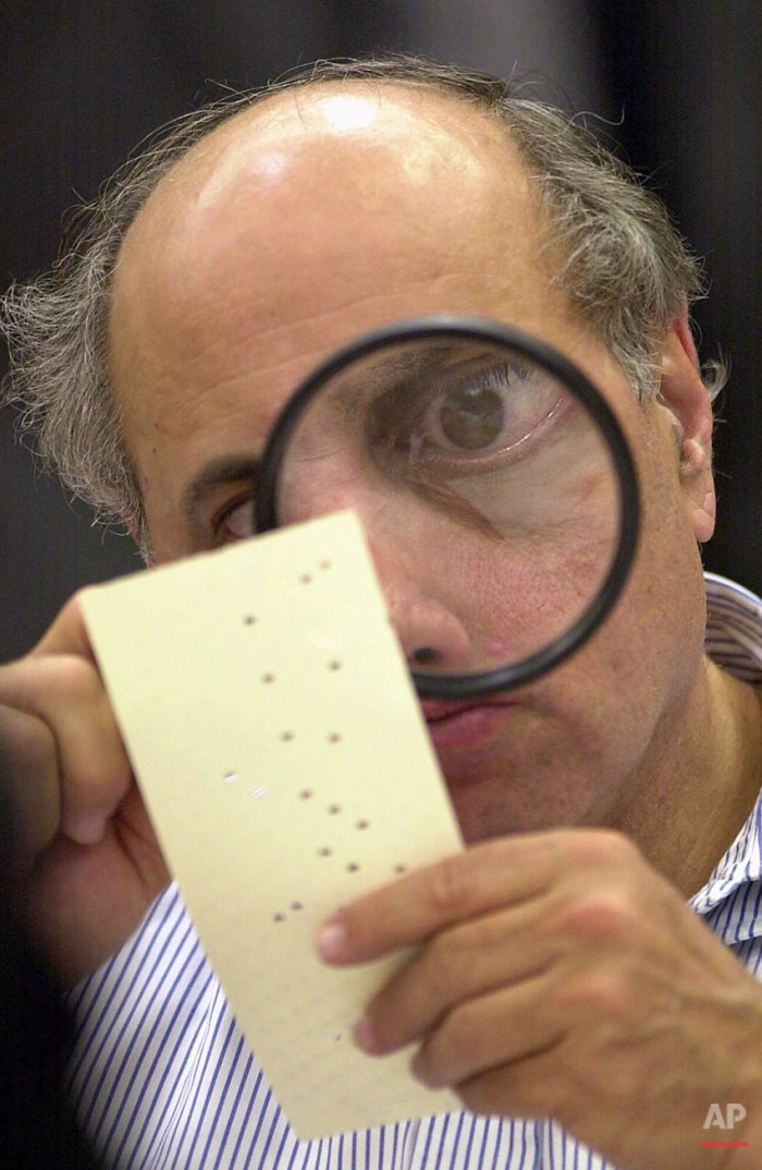 Broward County canvassing board member Judge Robert Rosenberg uses a magnifying glass to examine a disputed ballot Friday, Nov. 24, 2000, at the Broward County Courthouse in Fort Lauderdale, Fla. (AP Photo/Alan Diaz)
