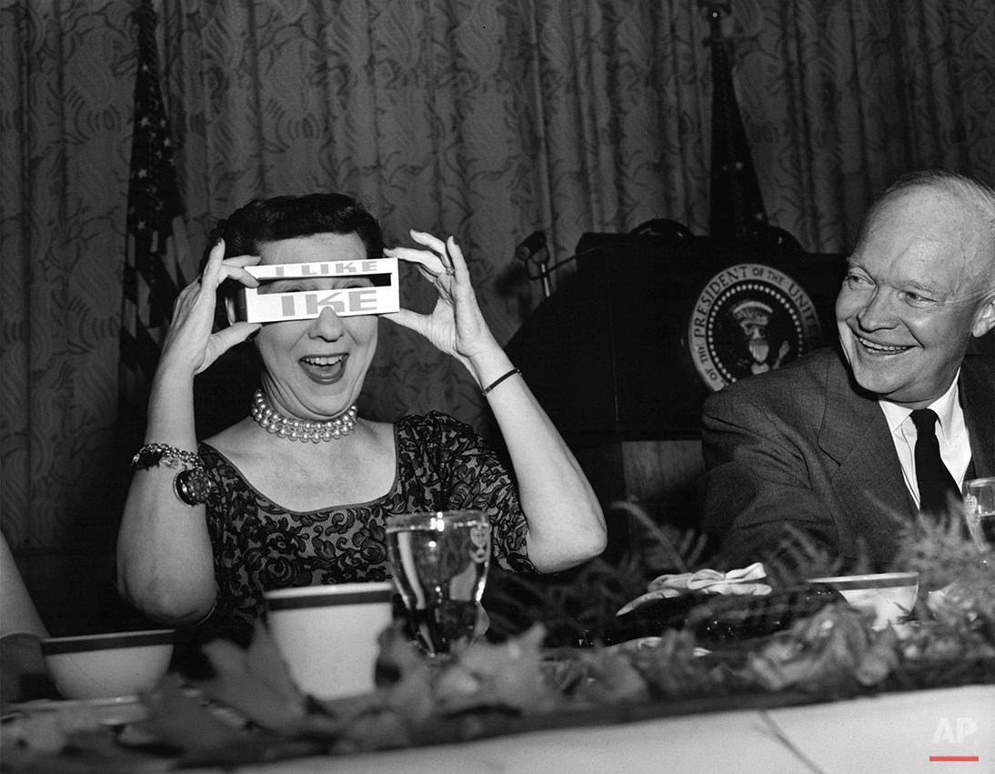 President Dwight D. Eisenhower laughs as his wife, Mamie, tries on a cardboard eyeshade during a Republican campaign dinner in Washington, April 17, 1956.  Eisenhower was preparing to run for his second term in office. (AP Photo/Bob Schutz)