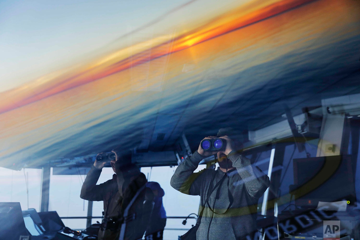 Researchers look toward the midnight sun while approaching the American island of Little Diomede, Alaska, and the Russian island of Big Diomede, as the Finnish icebreaker MSV Nordica sails along the international date line through the Bering Strait, Friday, July 14, 2017. The international date line is an imaginary border that runs through the middle of the Pacific Ocean and marks the boundary between calendar dates, effectively making it the zero-line for the planet's time zones. (AP Photo/David Goldman)
