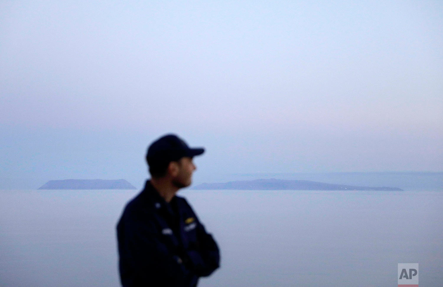 Cmdr. Bill Woityra, manager for domestic and polar icebreaking for the U.S. Coast Guard, looks out to sea while passing the American island of Little Diomede, Alaska, left, and the Russian island of Big Diomede, right, as the Finnish icebreaker MSV Nordica sails along the international date line through the Bering Strait, Friday, July 14, 2017. The international date line divides the two islands, so Little Diomede is sometimes referred to as Yesterday Isle and Big Diomede as Tomorrow Island. (AP Photo/David Goldman)