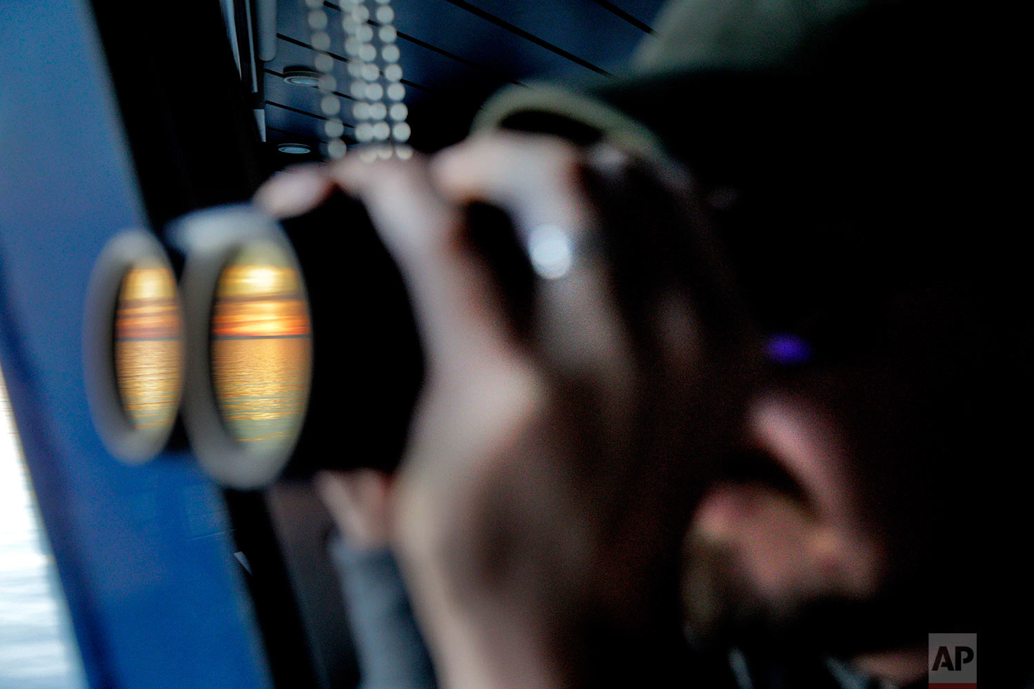 Researcher Ari Laakso looks to the horizon through binoculars under the midnight sun while approaching the Bering Strait, which divides the United States and Russia, as the Finnish icebreaker MSV Nordica sails along the international date line, Friday, July 14, 2017. The international date line is an imaginary border that runs through the middle of the Pacific Ocean and marks the boundary between calendar dates, effectively making it the zero-line for the planet's time zones. (AP Photo/David Goldman)