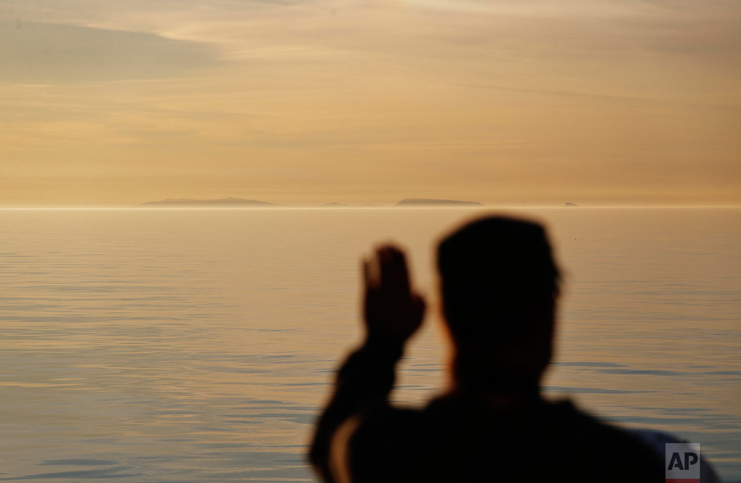 Researcher Ari Laakso shields his eyes from the midnight sun while approaching the American island of Little Diomede, Alaska, right, and the Russian island of Big Diomede, left, as the Finnish icebreaker MSV Nordica sails along the international date line through the Bering Strait, Friday, July 14, 2017. The international date line divides the two islands, putting them currently 20 hours apart despite roughly 2.4 miles (3.8 kilometers) between them. Due to this time difference, Little Diomede is sometimes referred to as Yesterday Isle and Big Diomede as Tomorrow Island. (AP Photo/David Goldman)