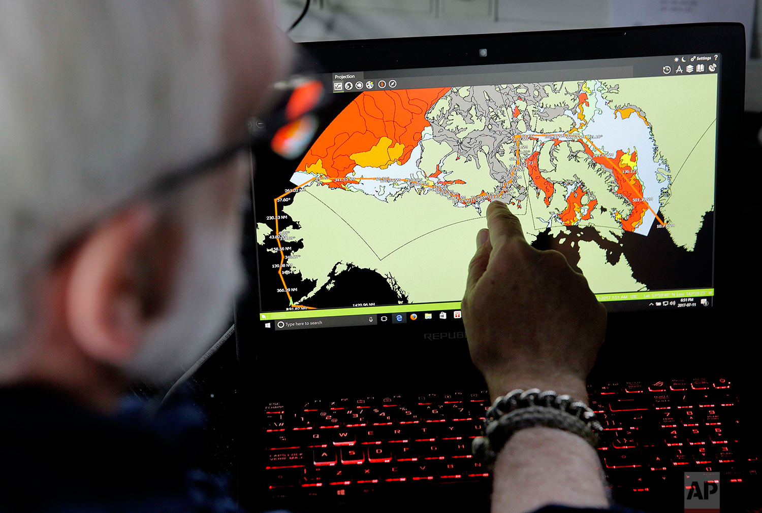 """Canadian ice navigator, David """"Duke"""" Snider shows the route the Finnish icebreaker MSV Nordica will navigate on a map of current sea ice conditions as the ship sails north in the Bering Sea Tuesday, July 11, 2017. A group of international researchers is sailing into the Arctic Sea aboard the Finnish icebreaker to traverse the Northwest Passage and record the environmental and social changes that are taking place in one of the most forbidding corners of the world. (AP Photo/David Goldman)"""