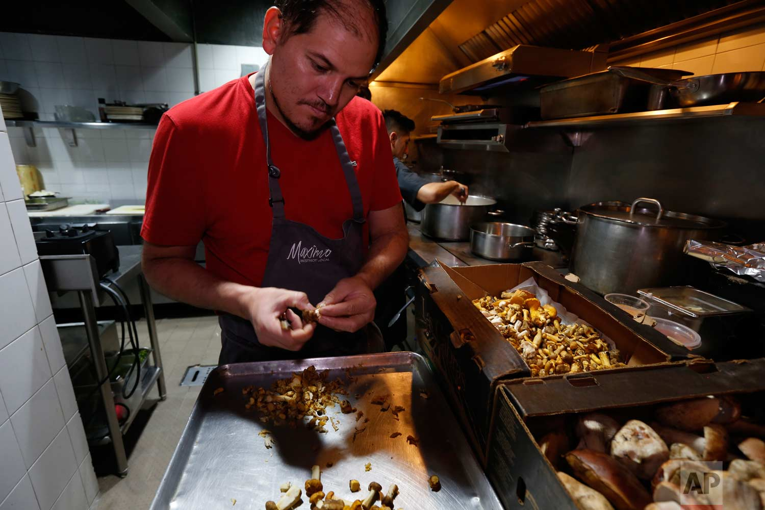 In this July 13, 2017 photo, chef Eduardo Garcia, founder of Maximo Bistrot and former migrant worker in the US, cuts mushrooms at his restaurant in Mexico City. (AP Photo/Marco Ugarte)