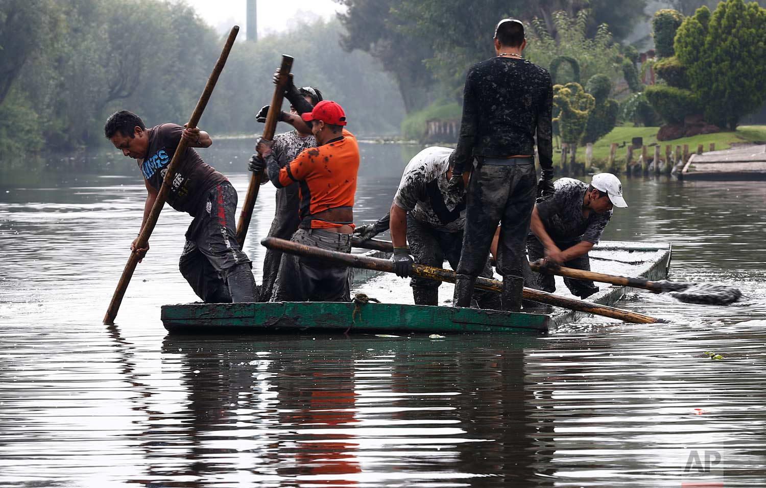 In this July 13, 2017 photo, men remove mud from a shallow channel so that tourist boats will be able to move through the channel, in Xochimilco, Mexico City. (AP Photo/Marco Ugarte)