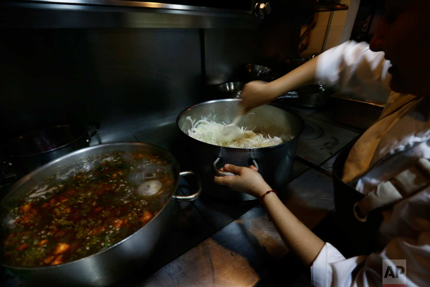 """In this July 13, 2017 photo, a kitchen staff worker cooks onions and beans with """"epazote"""" herbs at the Maximo Bistrot restaurant in Mexico City. (AP Photo/Marco Ugarte)"""