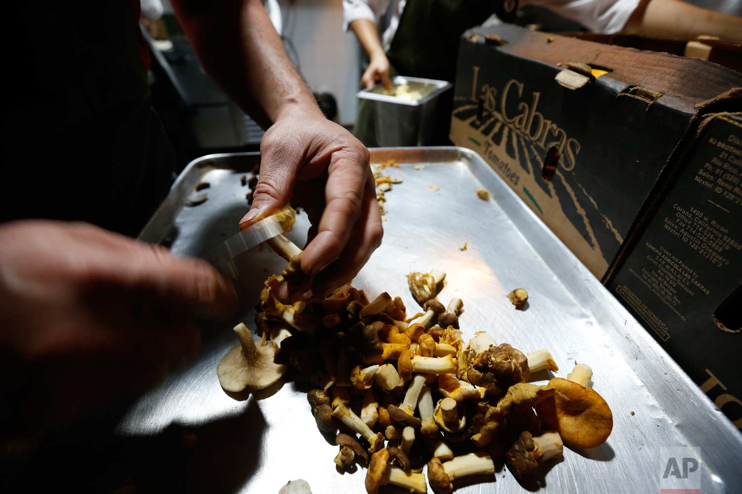 In this July 13, 2017 photo, chef Eduardo Garcia, founder of Maximo Bistrot and former migrant worker in the U.S., cuts mushrooms at his restaurant in Mexico City. (AP Photo/Marco Ugarte)