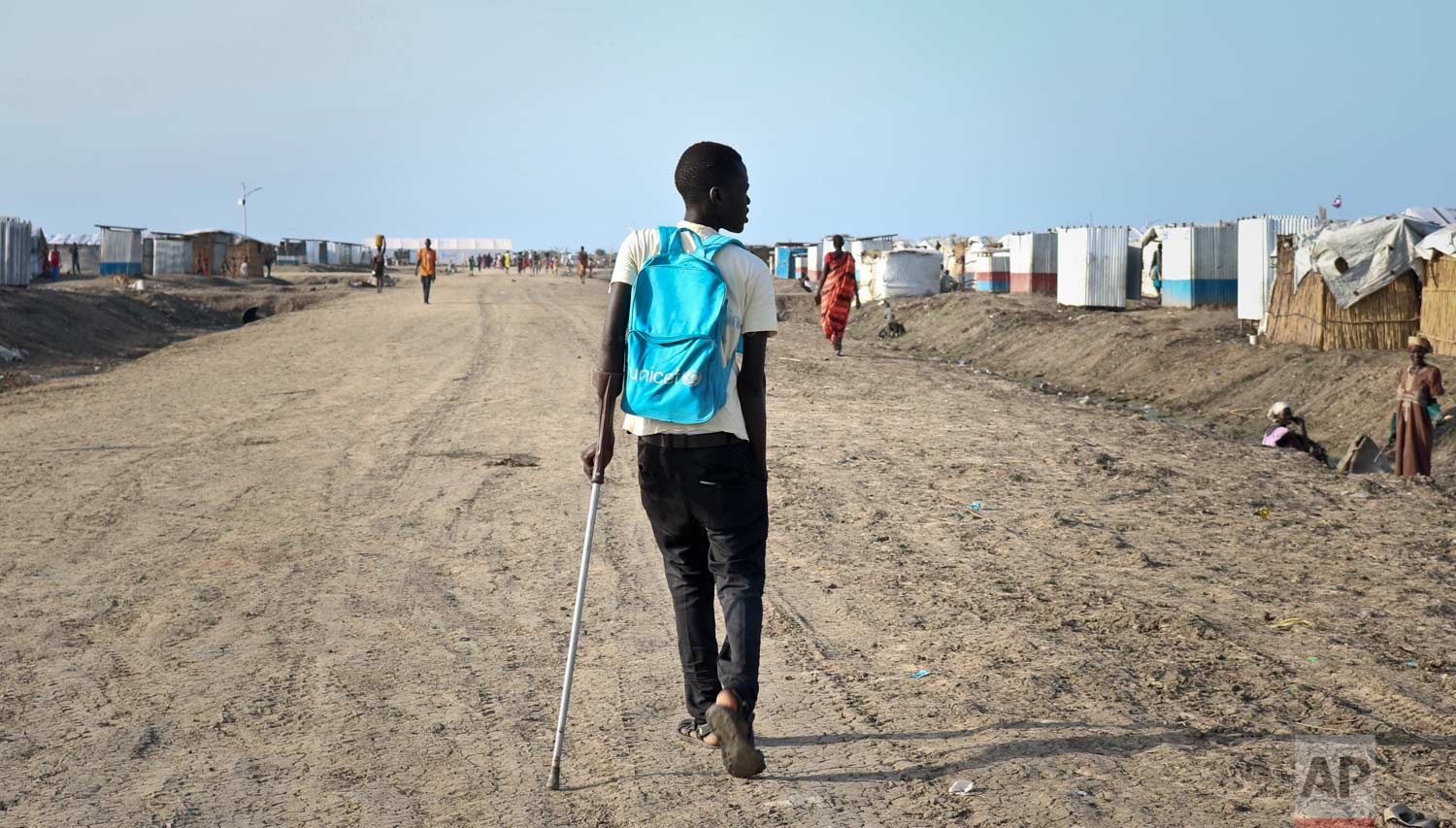 In this photo taken Monday, May 29, 2017, former child soldier James walks down the road from his small hut in a protection of civilians site to his first day at his new school, after recently being reunited with his mother who had thought he was dead, in Bentiu, South Sudan. (AP Photo/Sam Mednick)