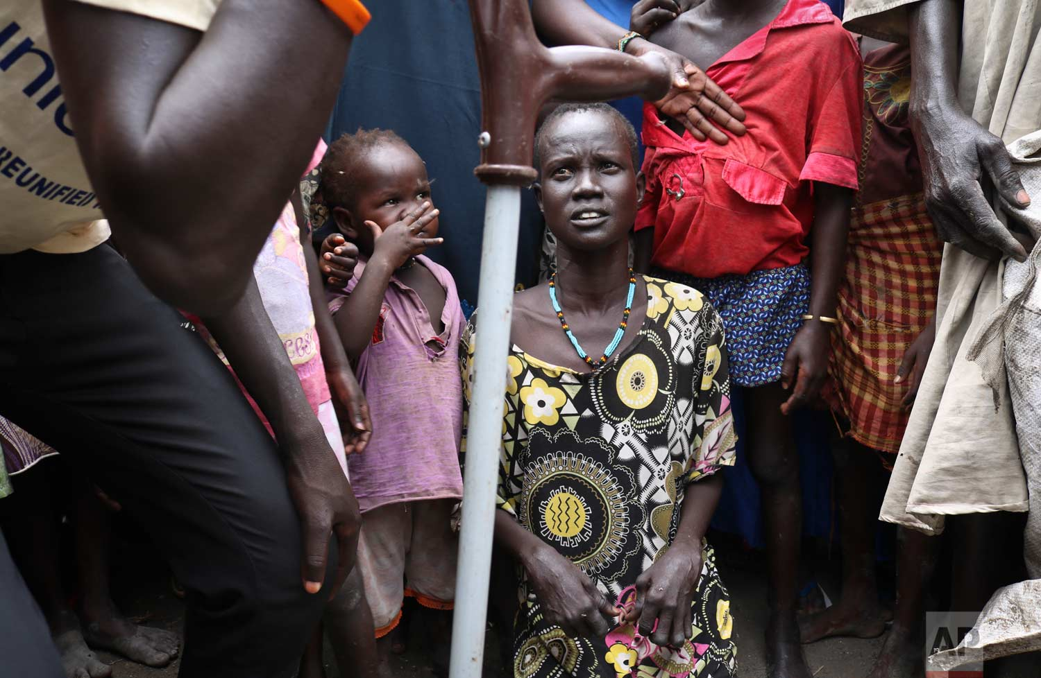 In this photo taken Friday, May 26, 2017, mother Nyayan Koang, who is unable to stand up due to polio, gazes at her son James, a former child soldier walking with a crutch, left, minutes after they were reunited and she saw him for the first time in 3 years, at a protection of civilians site in Bentiu, South Sudan. (AP Photo/Sam Mednick)
