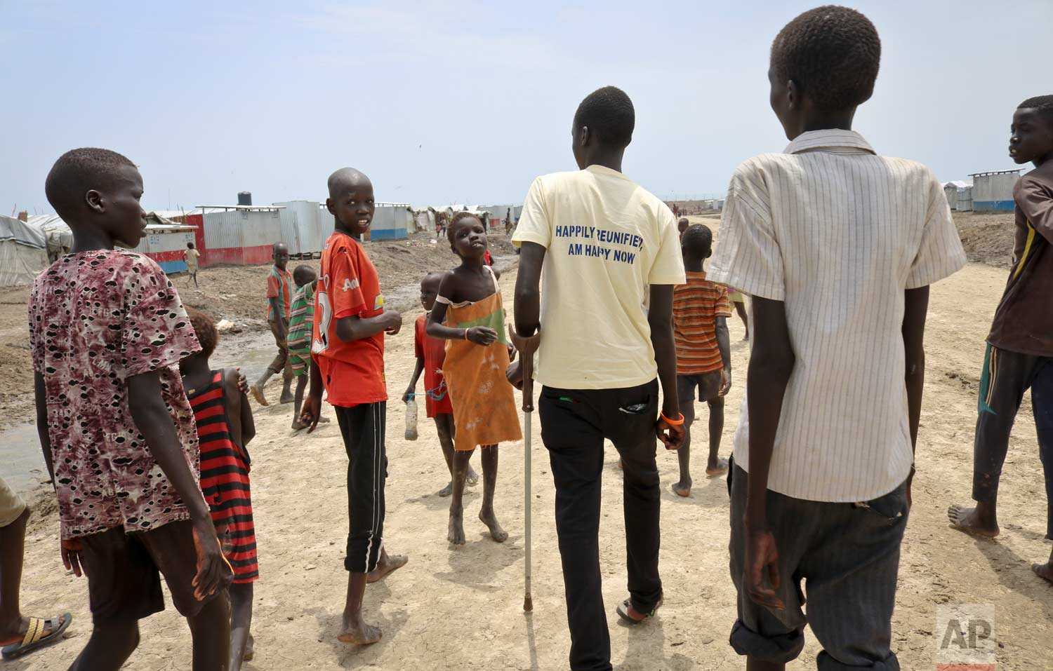In this photo taken Friday, May 26, 2017, former child soldier James, accompanied by one of his sisters and friends, walks towards his mother's house to be reunited and see her for the first time in 3 years, at a protection of civilians site in Bentiu, South Sudan. (AP Photo/Sam Mednick)