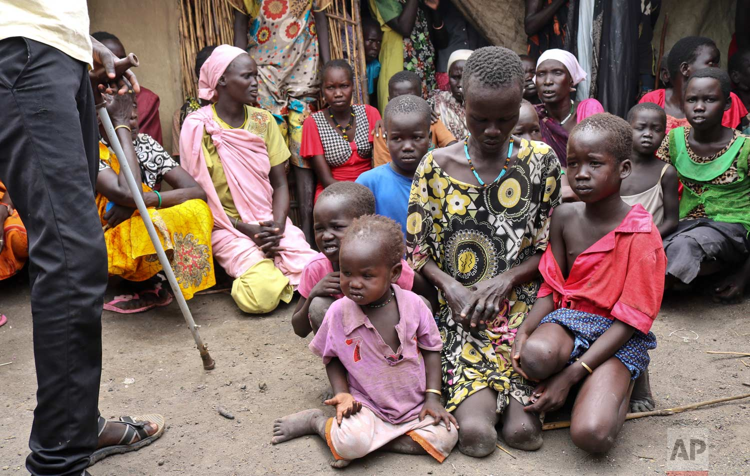 In this photo taken Friday, May 26, 2017, mother Nyayan Koang, who is unable to stand up due to polio, sits with her other children minutes after being reunited with her son James, a former child soldier walking with a crutch, left, and saw him for the first time in 3 years, in Bentiu, South Sudan. (AP Photo/Sam Mednick)