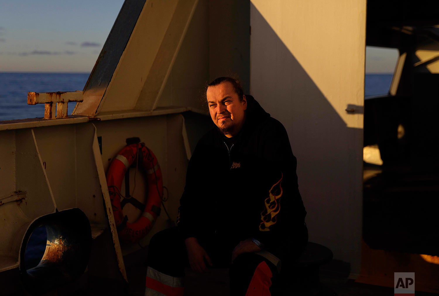 """Deck repairman Mika Koponen, 41, sits for a portrait aboard the Finnish icebreaker MSV Nordica as the ship sails the Amundsen Gulf in the Arctic, Wednesday, July 19, 2017. Koponen, who is making his first traverse through the Northwest Passage, started sailing at the age of 15 after following in his brother's footsteps. """"He was my idol. He sent me postcards from everywhere in the world,"""" said Koponen of his brother who passed away five years ago. """"After he became sick, I became his idol because he couldn't sail anymore. Now I'm taking these amazing adventures and I keep the tradition of the postcards. I think he'd be proud."""" (AP Photo/David Goldman)"""