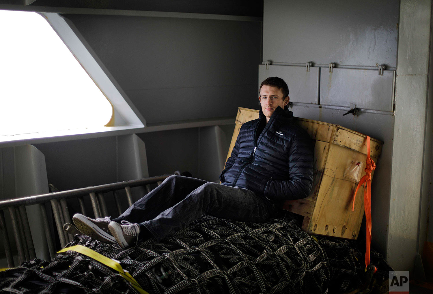 """Polar maritime lawyer Scott Joblin, 30, sits for a portrait aboard the Finnish icebreaker MSV Nordica as it sails north in the Bering Sea toward the Arctic, Wednesday, July 12, 2017. """"It's a chance to ground my research in real world context,"""" said Joblin who is pursuing his doctorate in international law at Australian National University. """"I don't think the size or the scale [of the Arctic] is anything you can comprehend. The trip so far contextualizes how hard it is to get there,"""" said Joblin of the roughly nine days the ship will take to reach the Arctic Circle from its departure in Vancouver. """"It's really the frontier as it exists."""" (AP Photo/David Goldman)"""